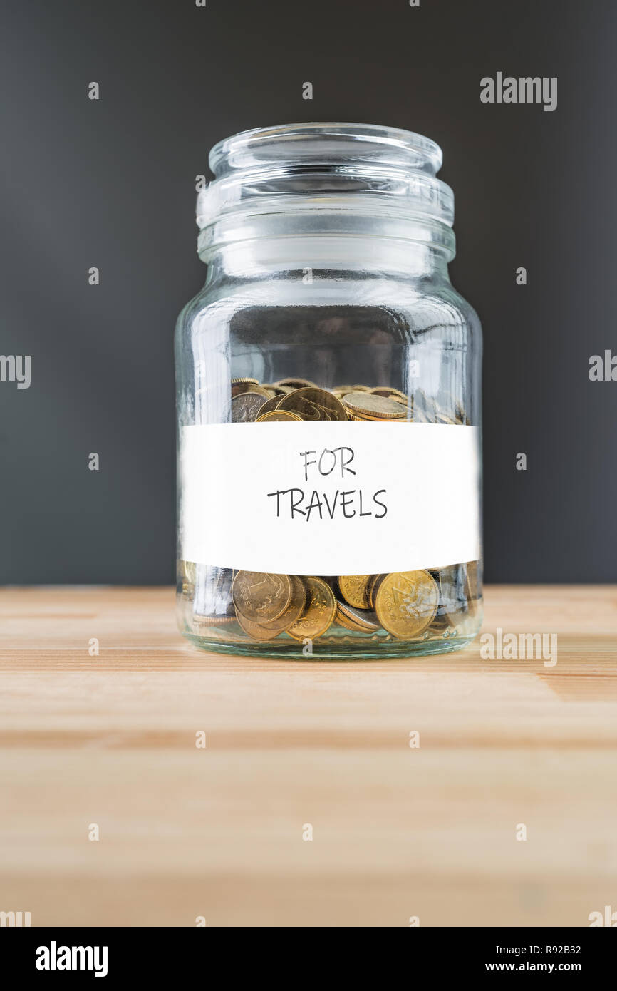 Jar with golden coins on natural wooden background. Money saving for travels abstract concept. Stock Photo