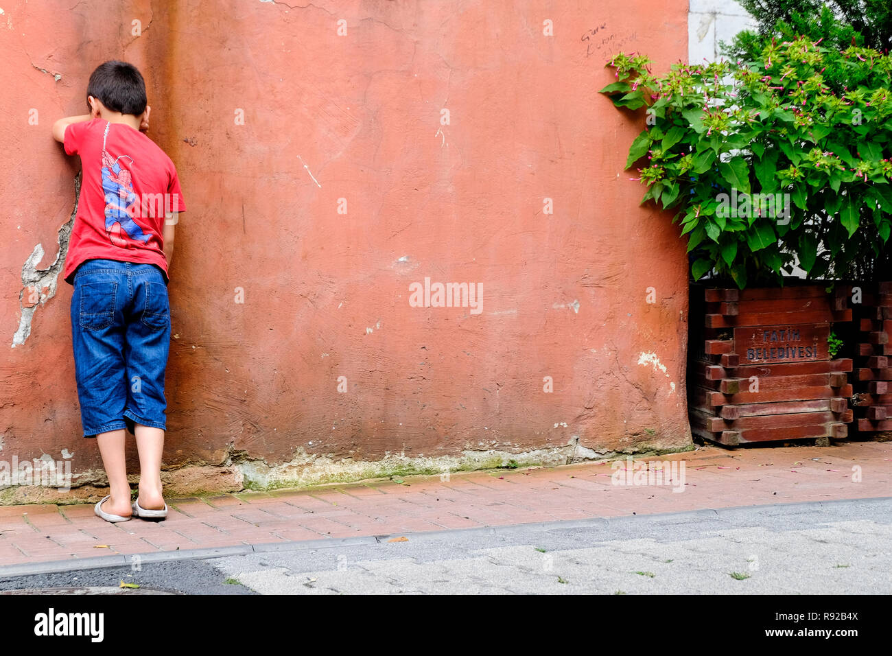 Young boy playing hide and seek in the street - Stock Image