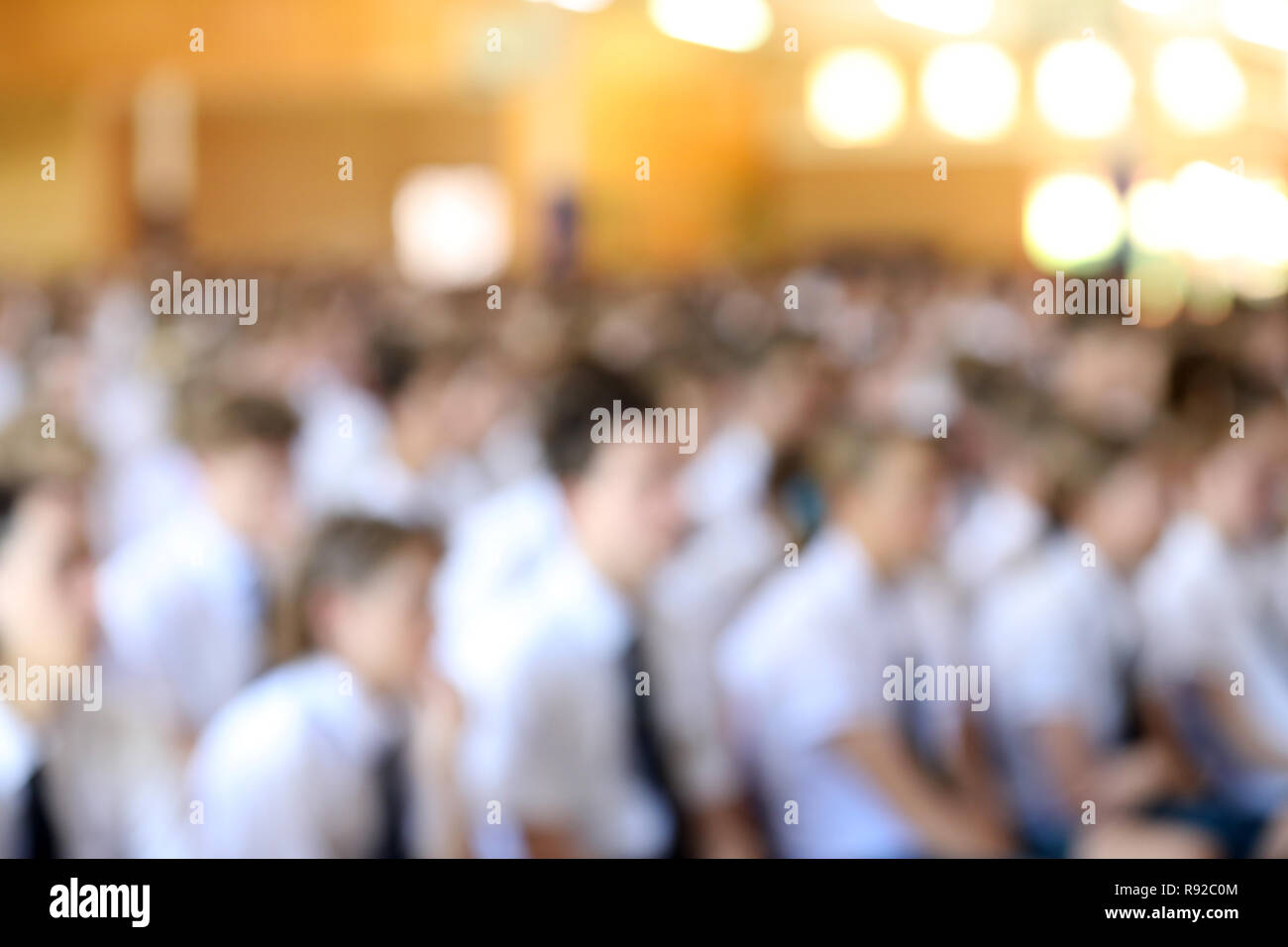 Deliberately out of focus blurred image of large hall full of high school students in white shirt and ties uniforms listening at assembly. - Stock Image
