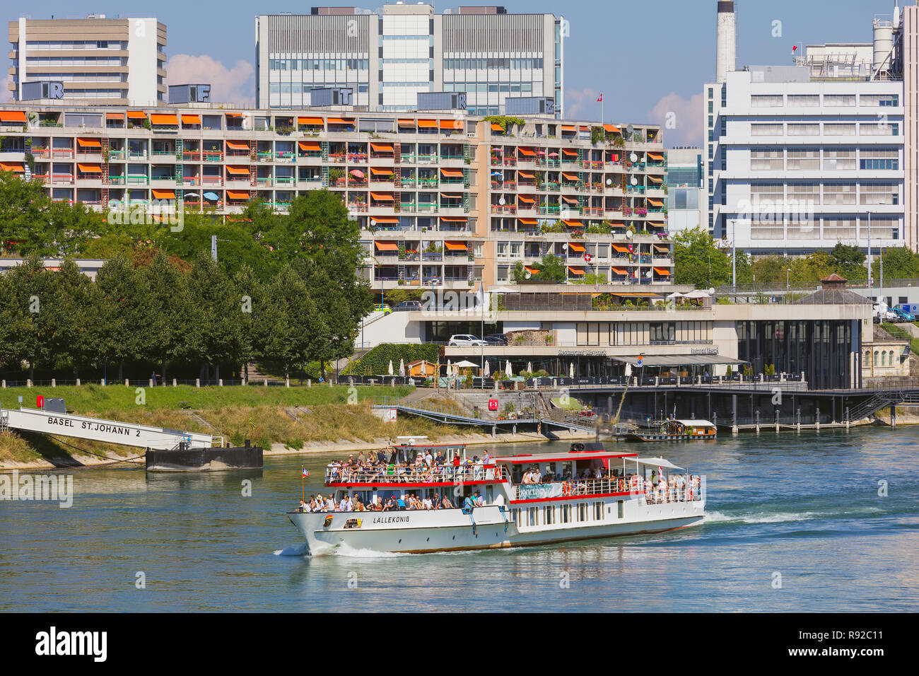 Buildings of  the city of Basel along the Rhine river, the Lallekonig boat with passengers on board passing Stock Photo