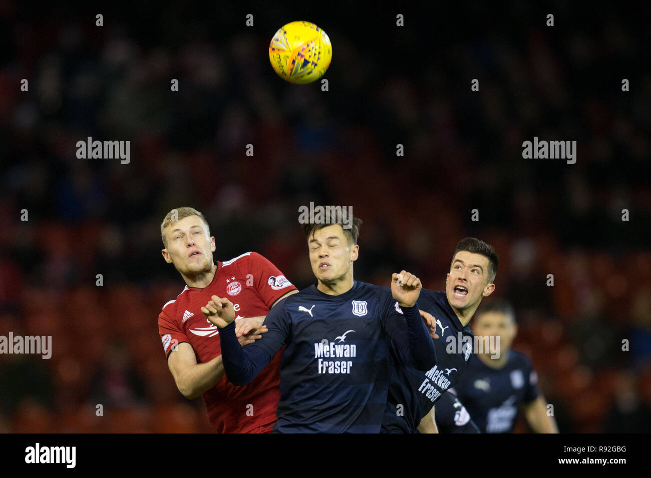 Pittodrie Stadium, Aberdeen, UK. 18th Dec, 2018. Ladbrokes Premiership football, Aberdeen versus Dundee; Sam Cosgrove of Aberdeen competes in the air with Jesse Curran and Cammy Kerr of Dundee Credit: Action Plus Sports/Alamy Live News - Stock Image