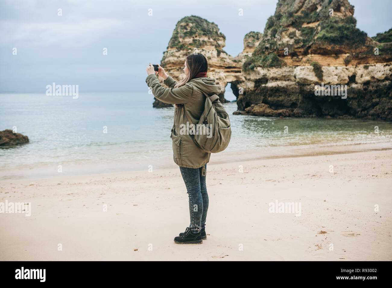Girl tourist with a backpack photographing a beautiful landscape standing on the Atlantic coast. Stock Photo