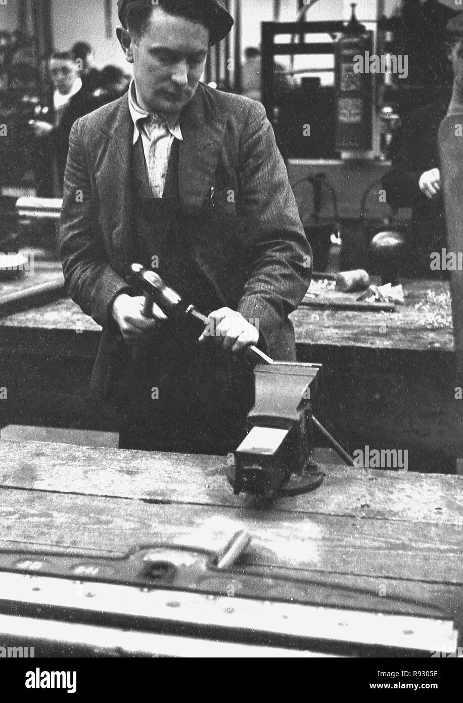 1940s, historical, inside a workshop, at a workbench, an unemployed Welsh miner trying out a new skill, metalwork, Merthyr, Wales. - Stock Image