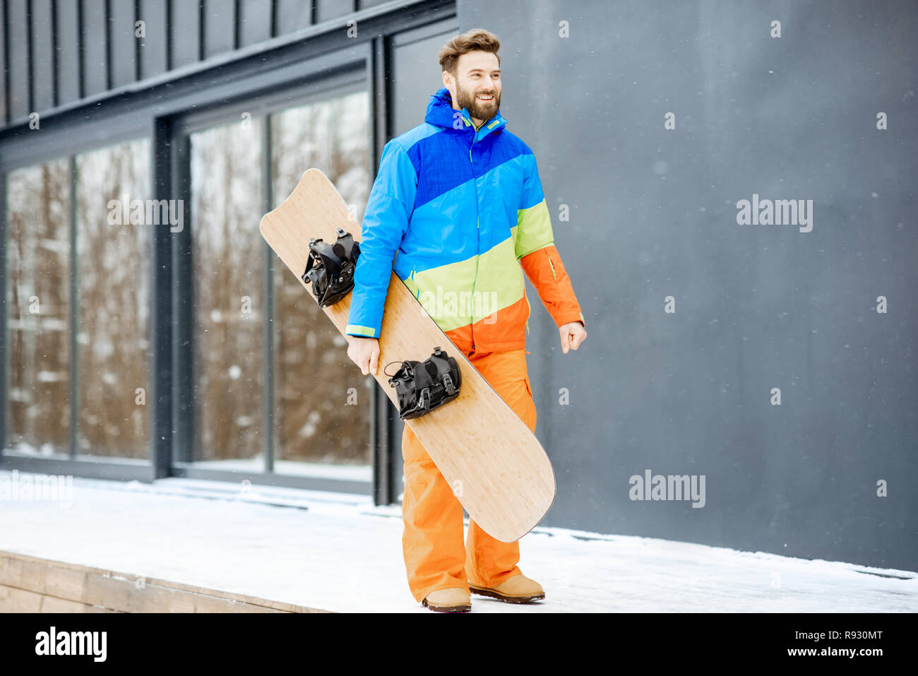 Man in ski suit with snowboard near the modern house or hotel in the mountains - Stock Image