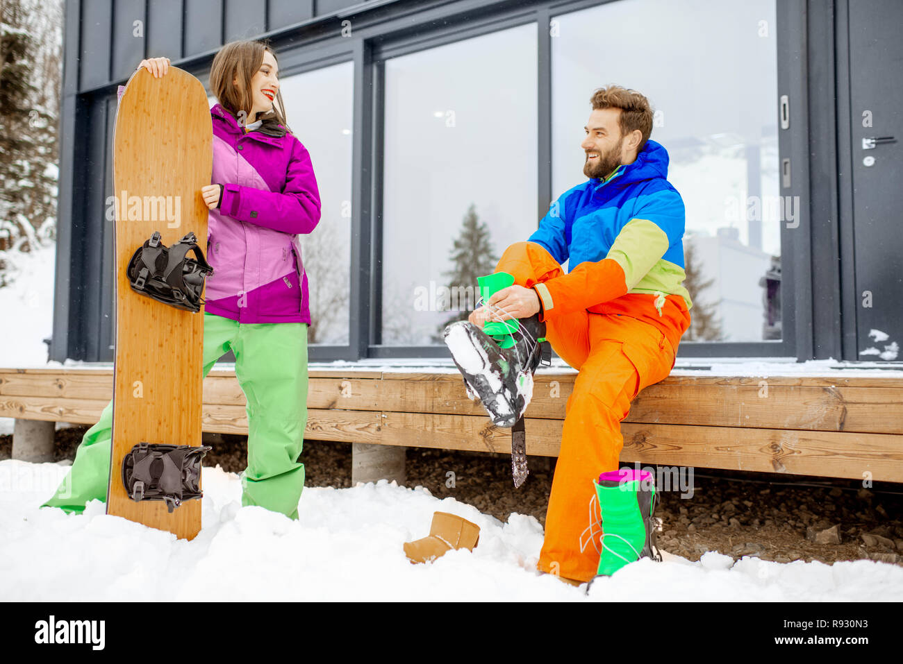 Young couple in ski suits preparing for snowboarding sitting on the terrace of the modern house in the mountains - Stock Image