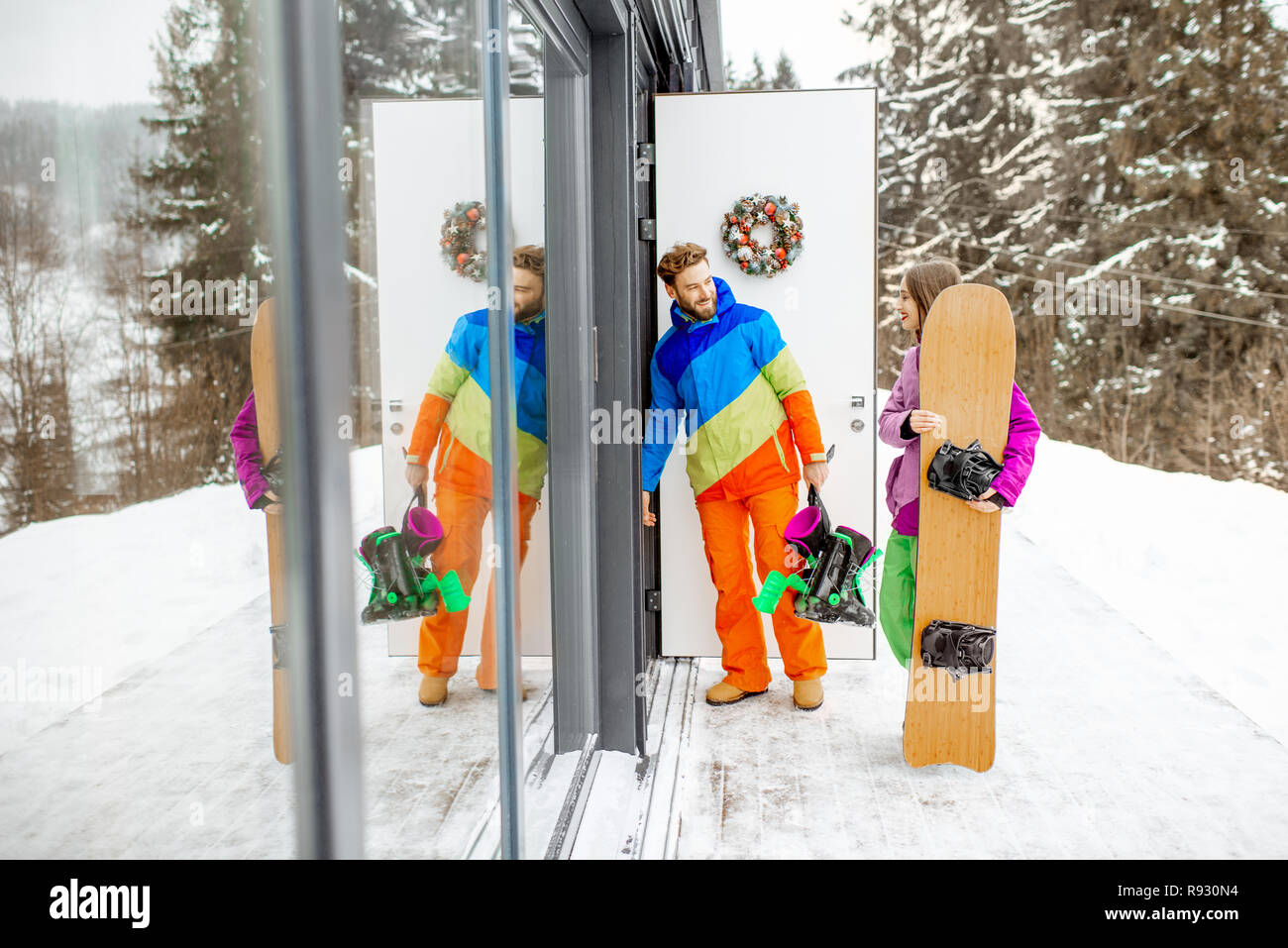 Young couple in coloful ski suits entering home or hotel after snowboarding in the snowy mountains - Stock Image