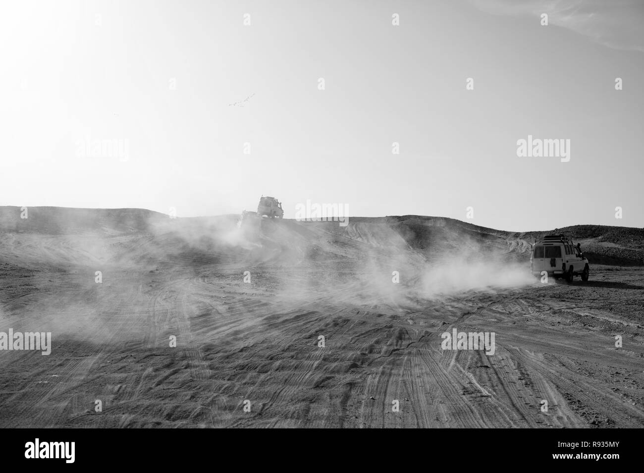 Competition racing challenge desert. Car overcome sand dunes obstacles. Car drives offroad with clouds of dust. Offroad vehicle racing obstacles in wilderness. Endless wilderness. Race in sand desert. - Stock Image