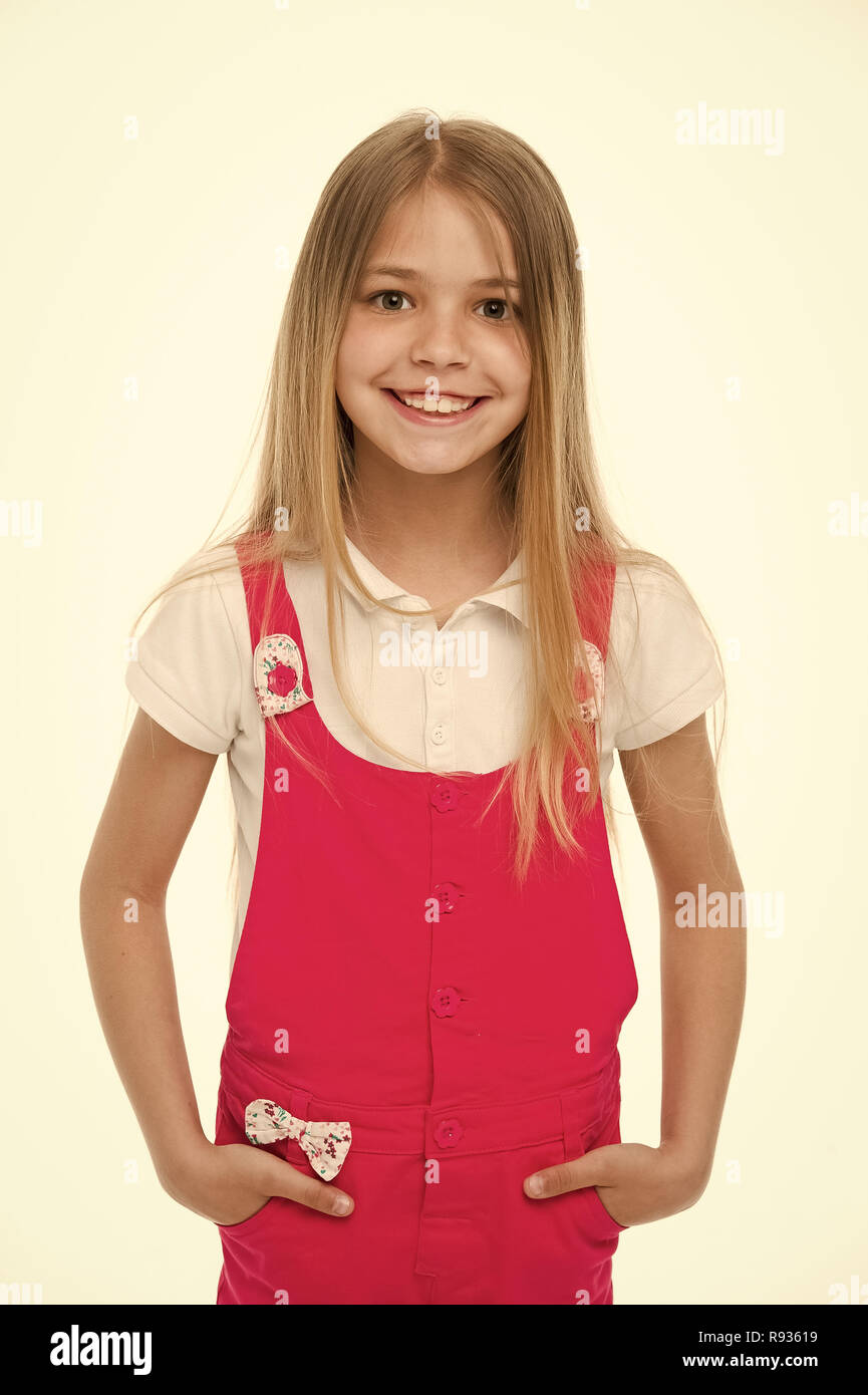 Child smiling with long blond hair. Small girl smile in pink jumpsuit isolated on white. Kid model in fashionable overall. Fashion style and trend. Happy childhood and childcare. - Stock Image