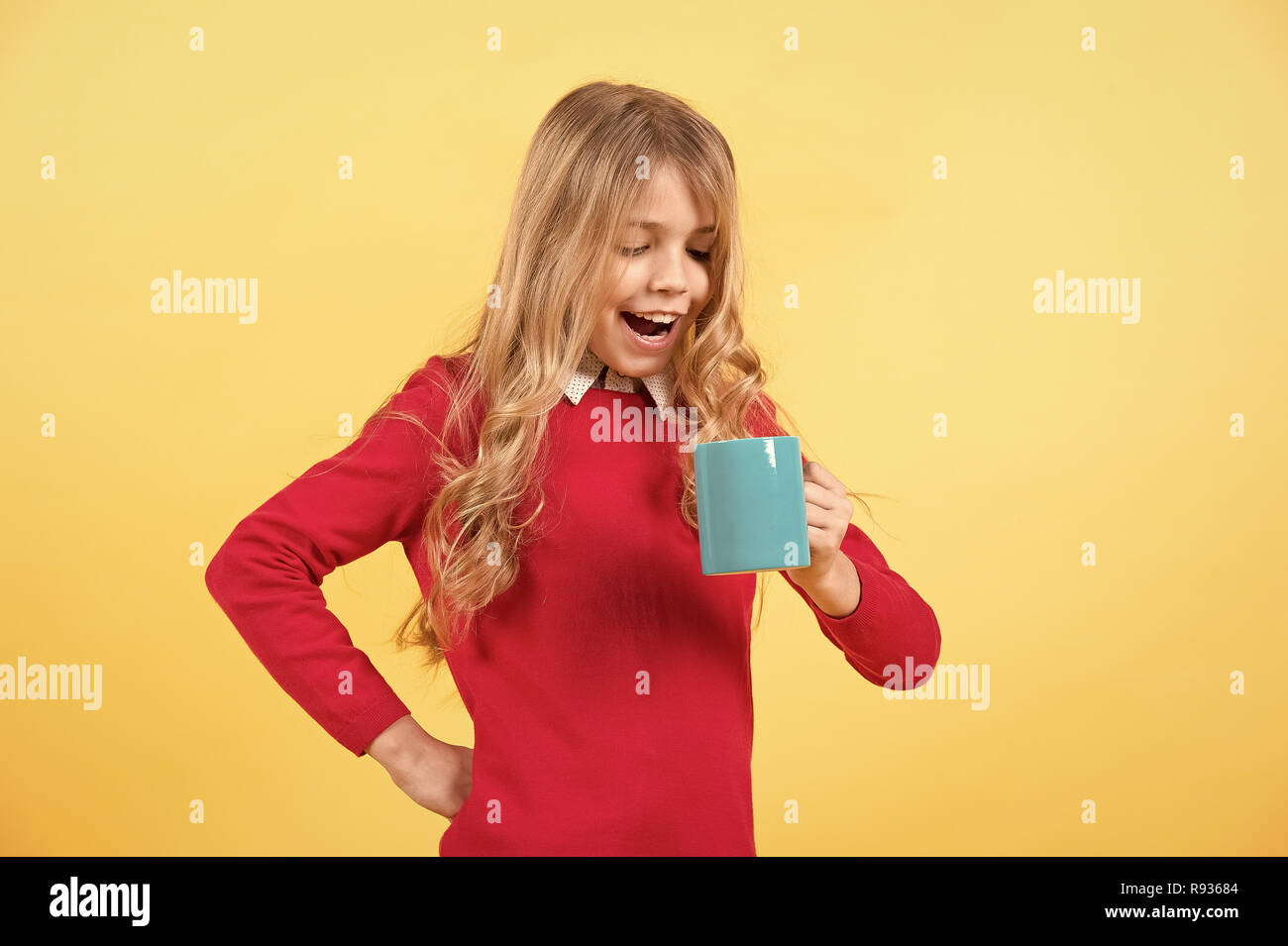 Tea or coffee break. Girl with long blond hair in red sweater hold mug. Child smile with blue cup on orange background. Thirst, dehydration concept. Health and healthy drink. - Stock Image