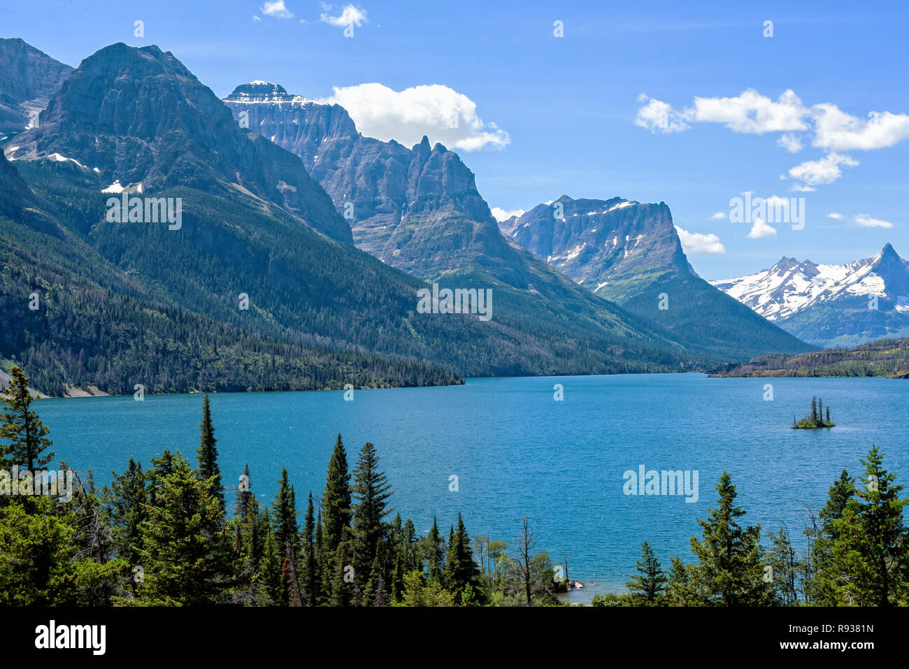 Wild Goose Island in Glacier National Park with Mountain Peaks in the Background - Stock Image