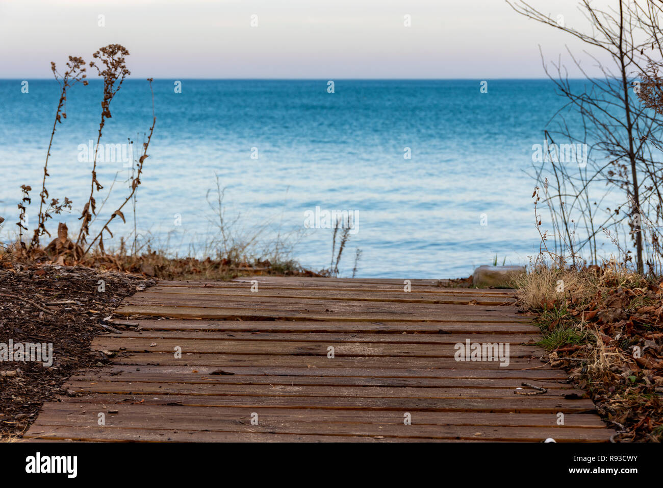 Daylight shot of a walkway that leads straight the beach on Lake Michigan. - Stock Image