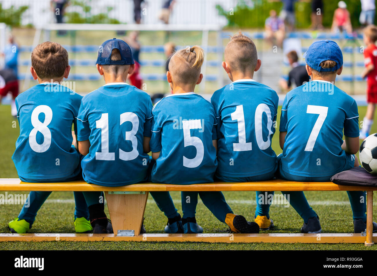 Children's Football Team During the Match.  Boys Football Team Members Sitting on Soccer Bench on the Grass Field. Kids Football Team with Ball on the - Stock Image