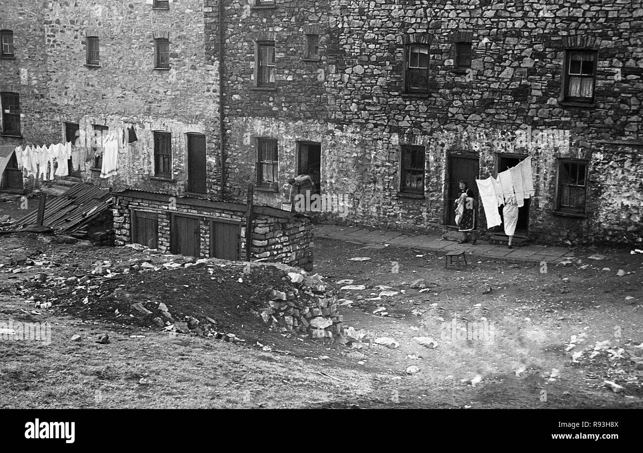 Mid-1940s, slum housing in Merthyr, South Wales, UK. The decline of the local steel and coal industries in the 1930s and then again following WW2 meant migration and unemployment and the area suffered great poverty and hardship, with poor housing stock and living conditions.Here we see local women putting their washing on a clothes line outside their cottages. - Stock Image