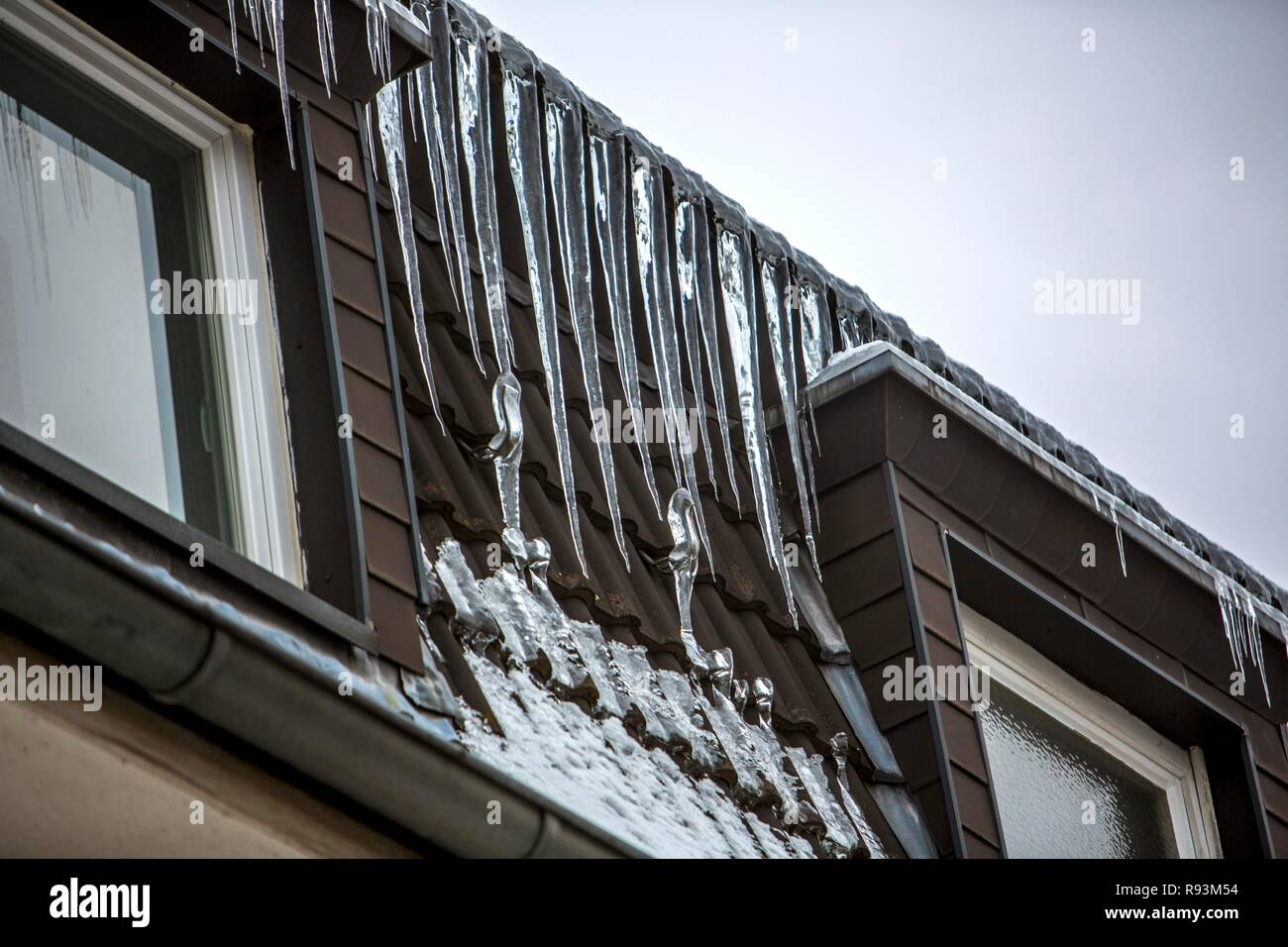 Large icicles hanging from the eaves of a house, sign of a poorly heat-insulated roof, Essen, North Rhine-Westphalia, Germany - Stock Image
