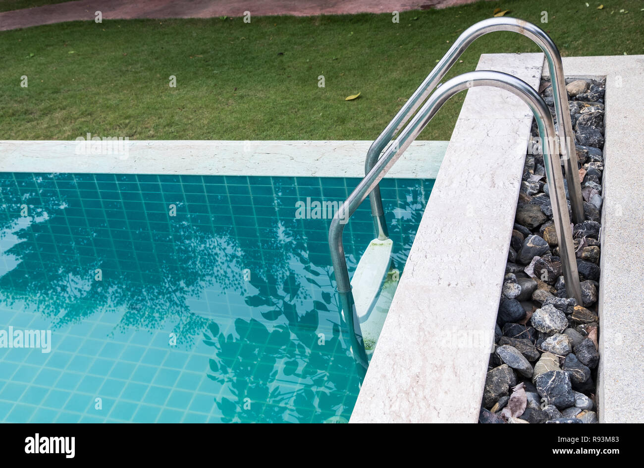 Metal rail of the ladder in the clear swimming pool in the tropical ...