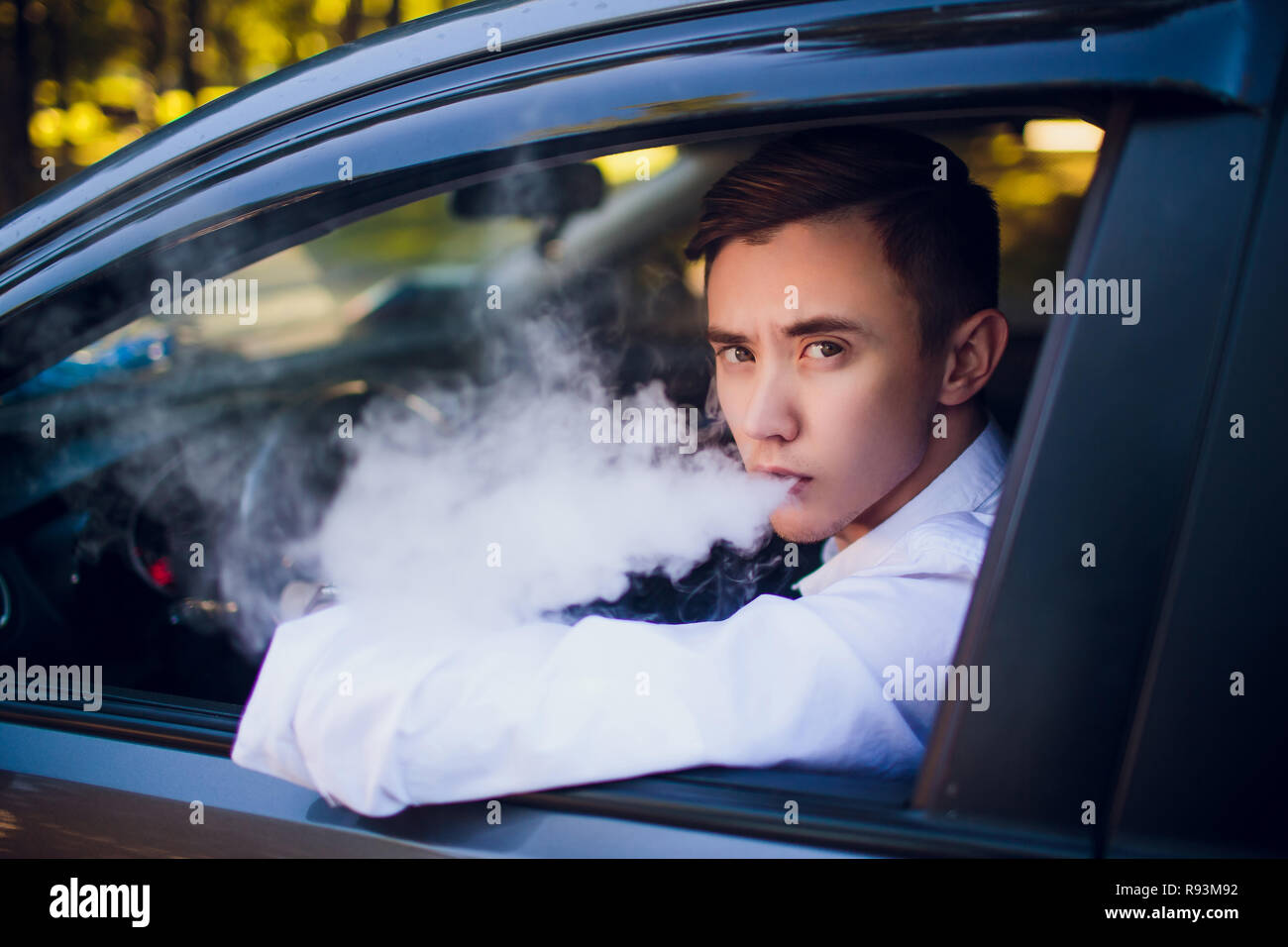 View from side young man smoking an e-cigarette as he drives his car on an urban street. car driver peeps out of the car and smokes - Stock Image