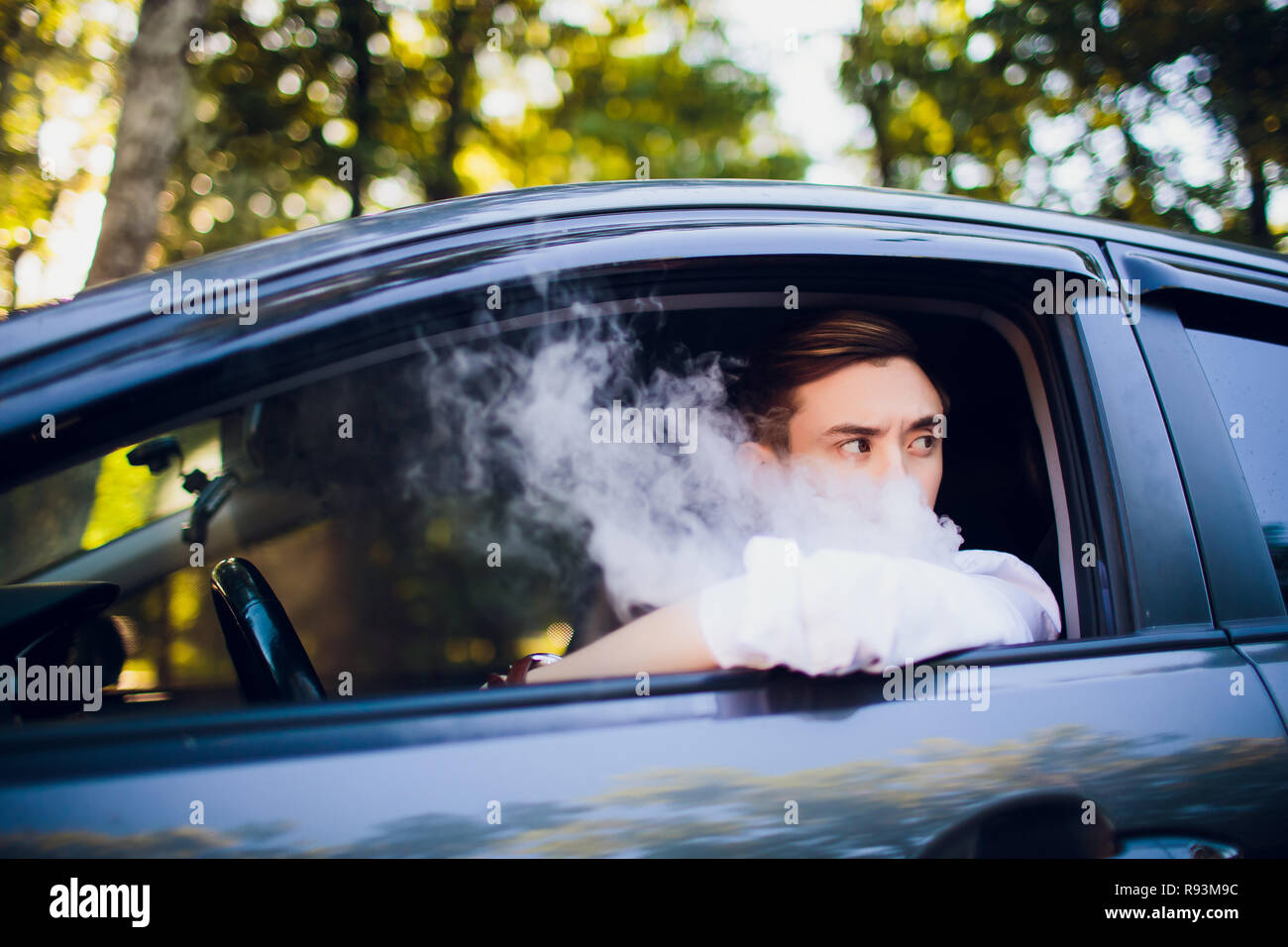 View from side young man smoking an e-cigarette as he drives his car on an urban street. car driver peeps out of the car and smokes Stock Photo