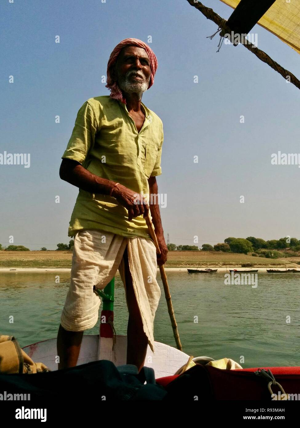 An old boatman steering a sailing boat on the Ganges River in India - Stock Image
