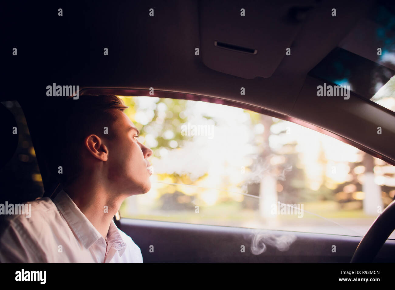 View from side young man smoking an e-cigarette as he drives his car on an urban street - Stock Image