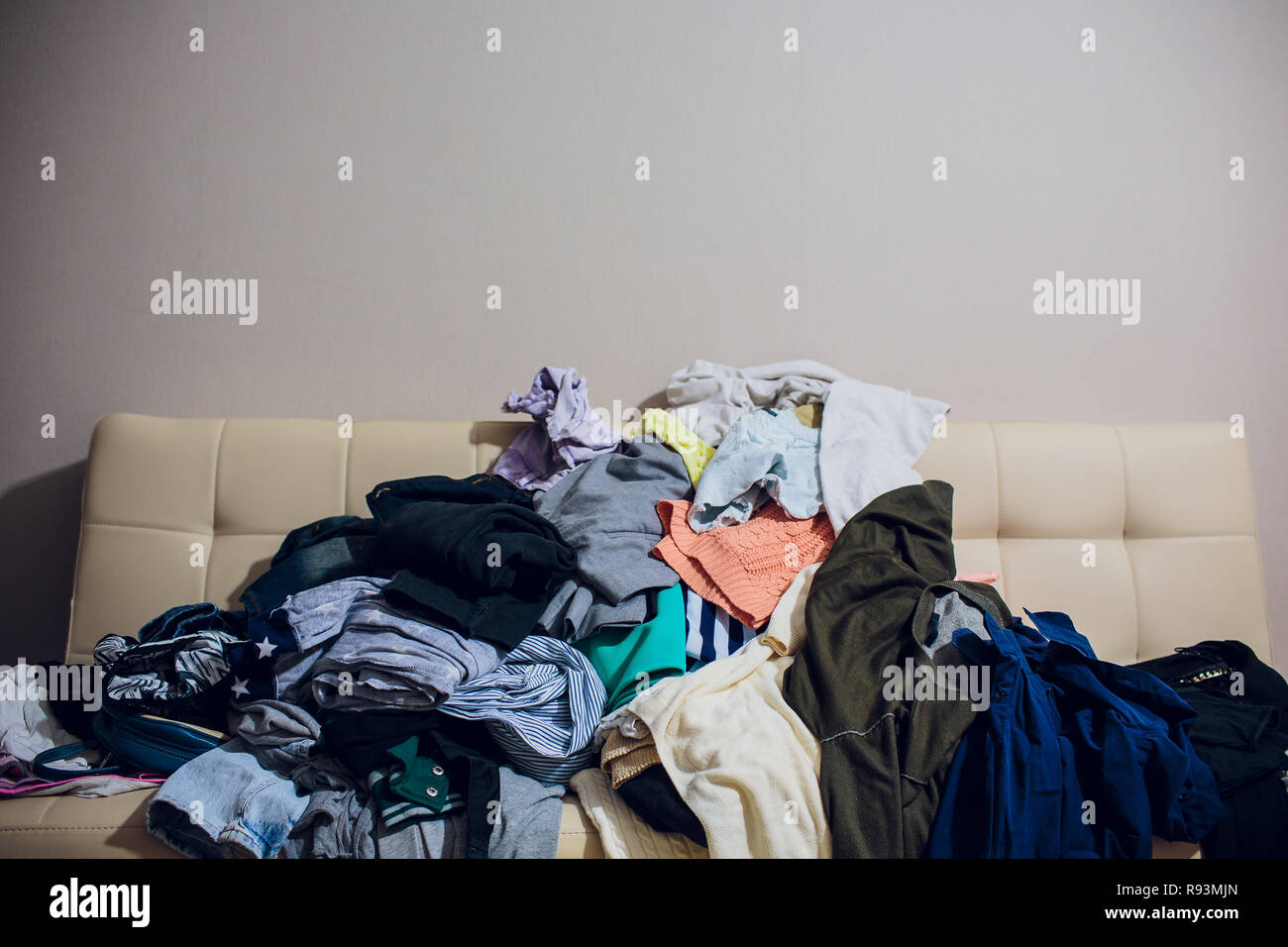 Messy clothes, lady bag and shoes scattered on leather sofa - Stock Image