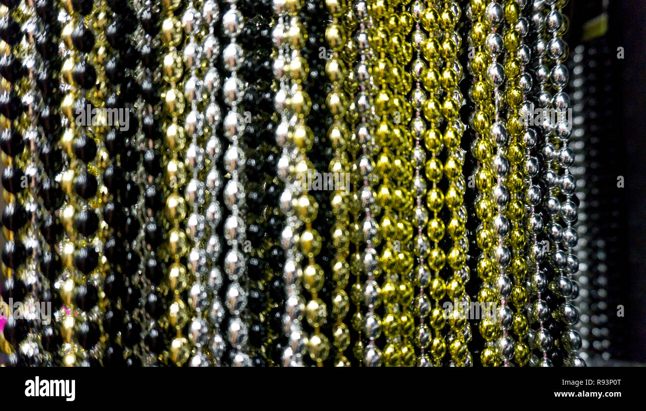 Many black, white, silver, gold and golden beads party neacklaces for New Years celebrations or background. Macro close up horizontal photo vertical neacklace Stock Photo