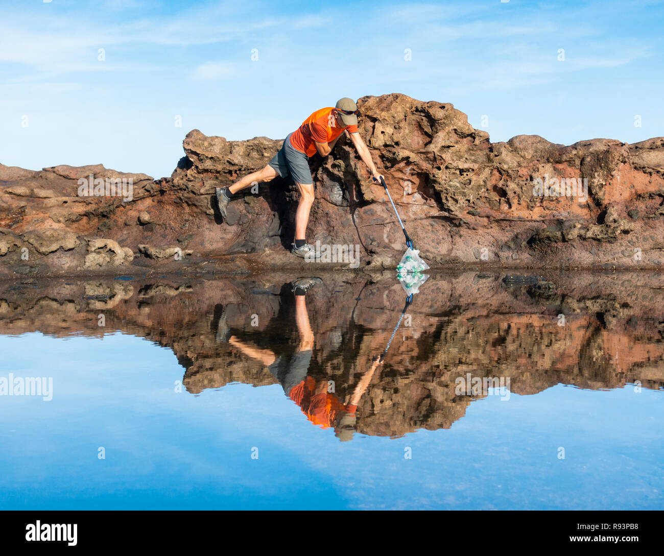 A Plogger/jogger collects plastic rubbish from beach during his morning run - Stock Image
