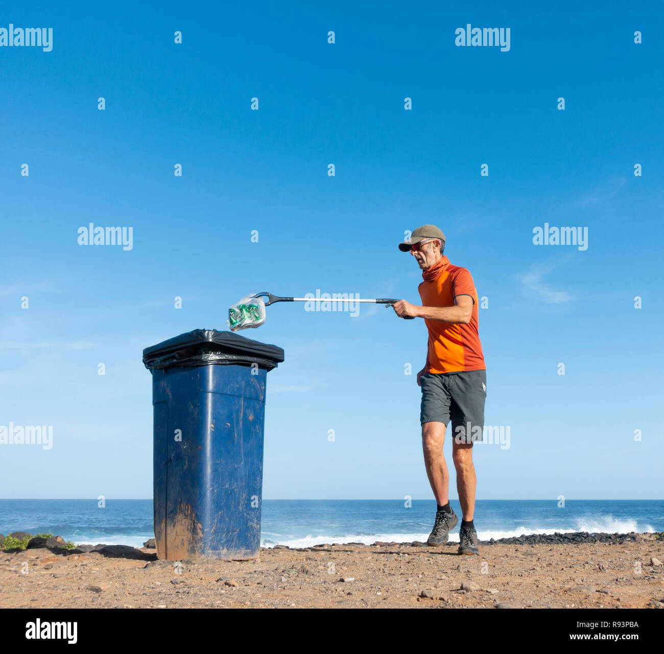 A Plogger/jogger collects plastic rubbish from beach during his morning run Stock Photo