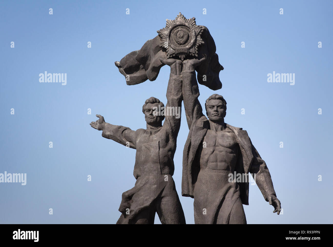 Statue of Sovjet realism: two young men of black stone holding up a CCCP medallion, Kiev, Ukraine - Stock Image
