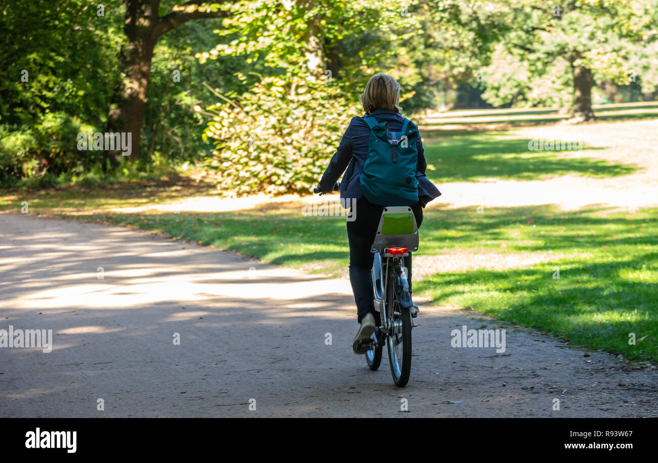 Healthy lifestyle. Woman is riding a bicycle in a path of Tiergarten park, Berlin, Germany. Nature background. Stock Photo