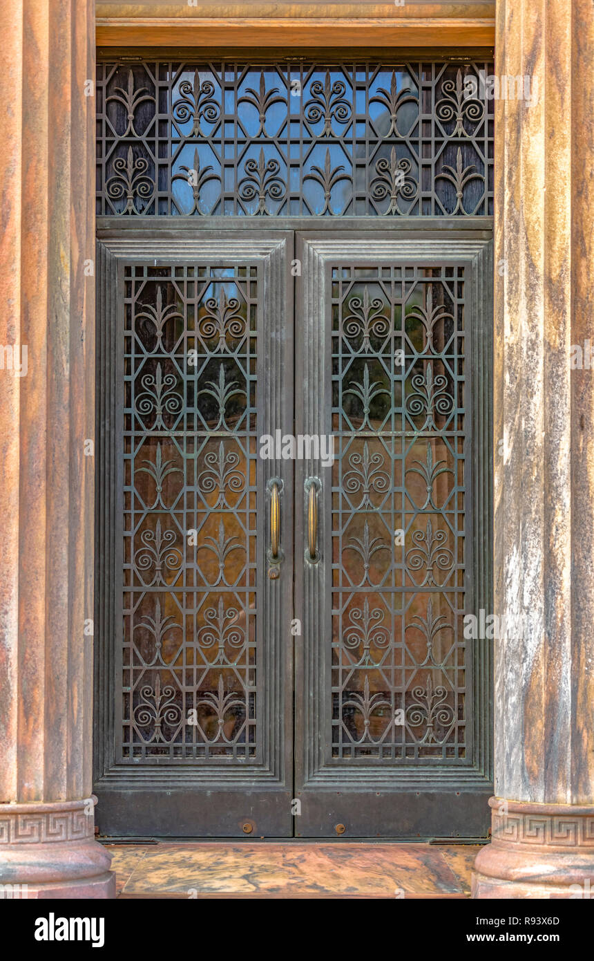 Ornate iron door framed by vertical fluted columns - Stock Image