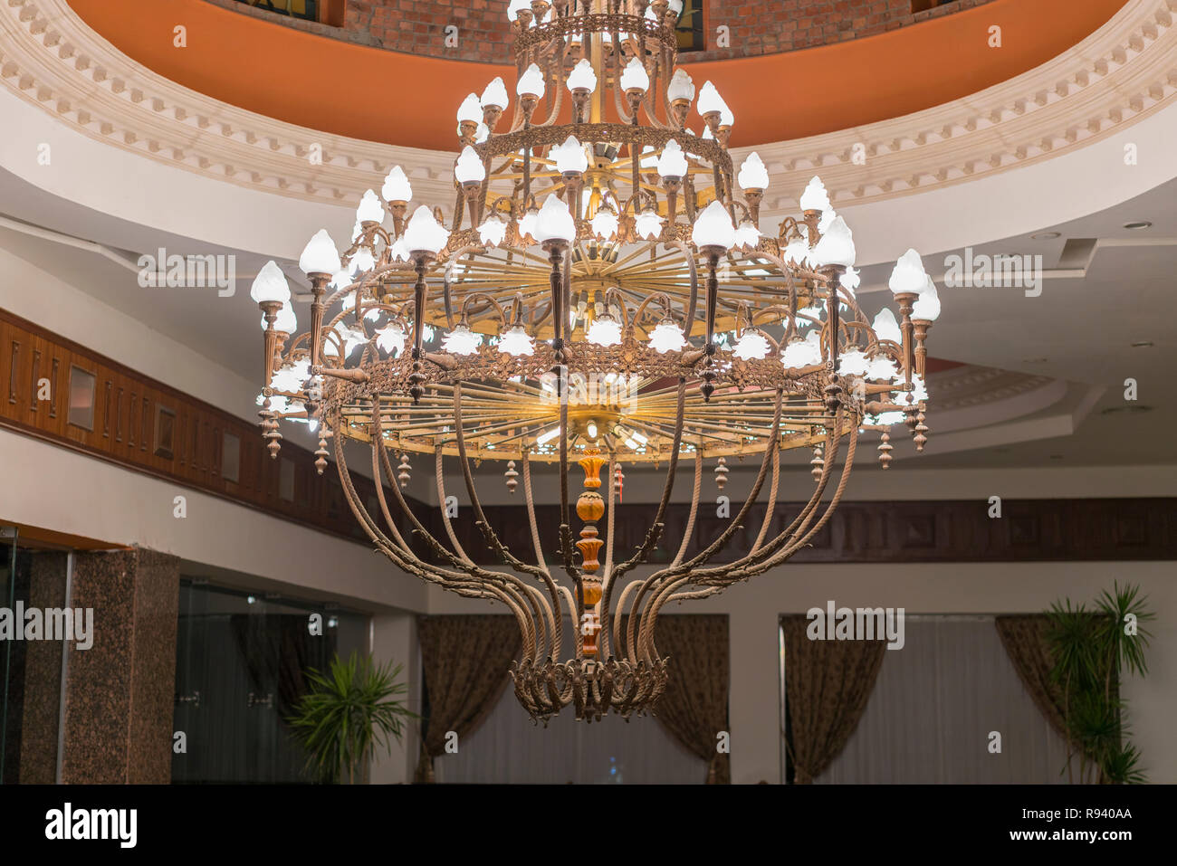 Huge chandelier in the hall. Chandelier on decoarted ceiling of a ballroom. Stock Photo
