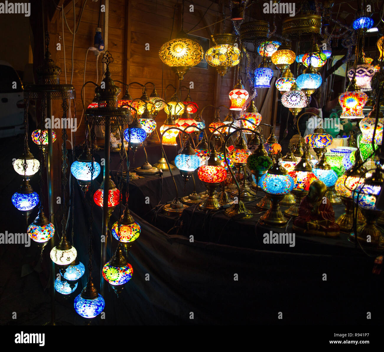 Various colorful round shaped retro glass lamps in darkness, in the market, as vintage color effect - Stock Image