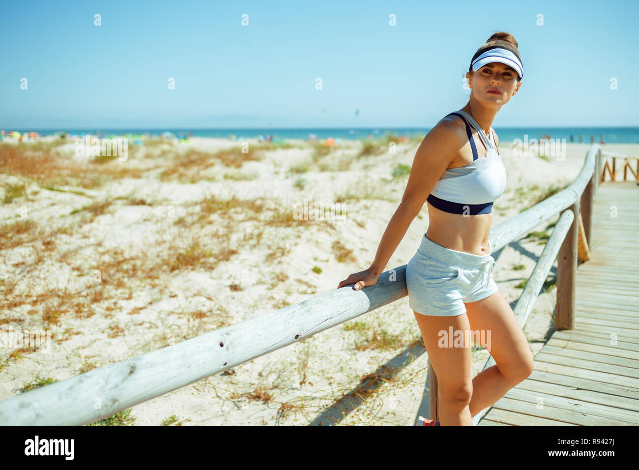 fit woman jogger in fitness clothes on the beach looking