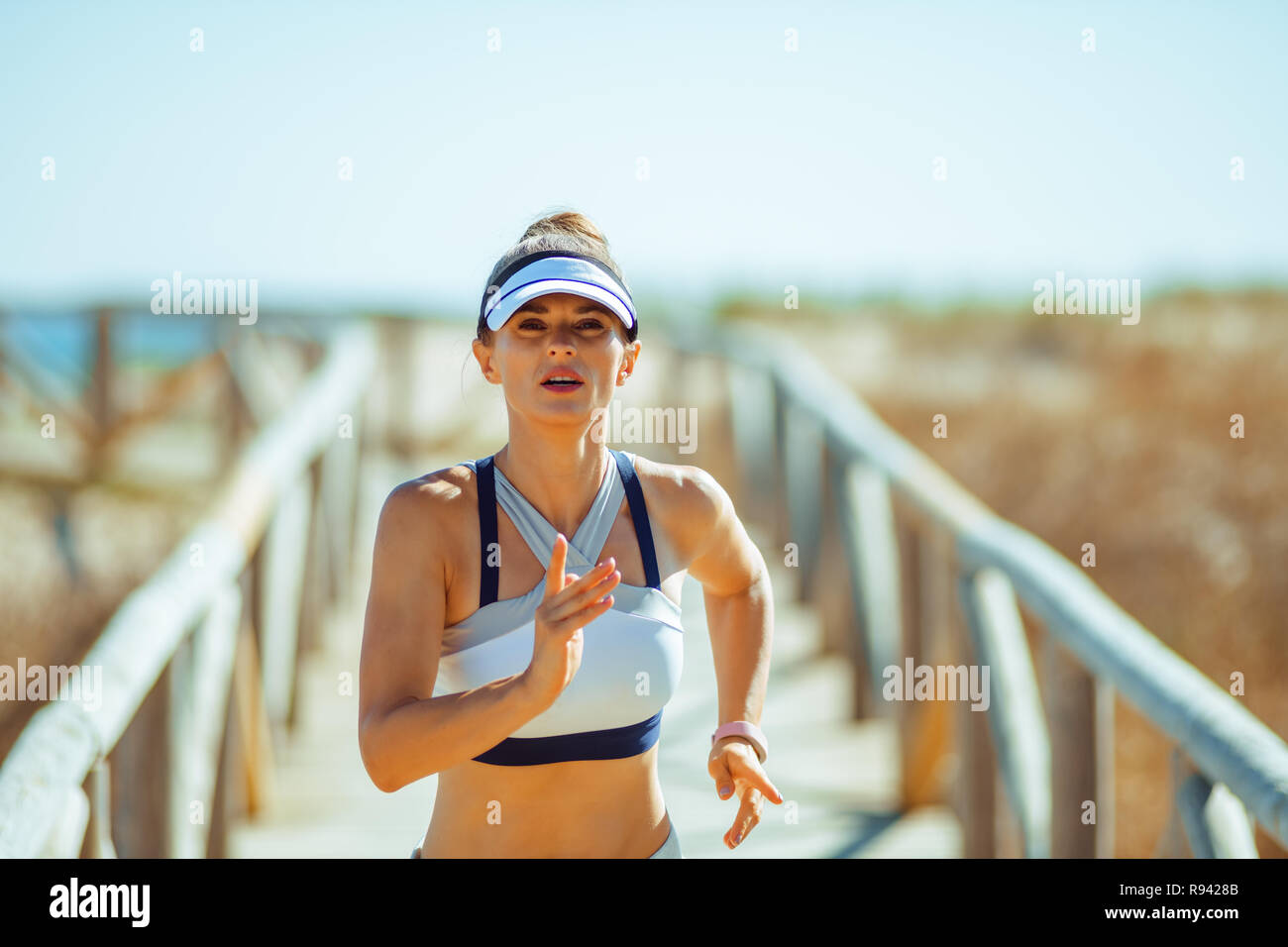 healthy sports woman in sport clothes on the beach jogging. you can workout anywhere. Outdoor exercise provides an opportunity to be physically active - Stock Image