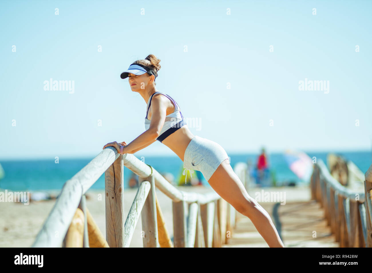 young woman jogger in sport clothes on the beach doing pushups  30