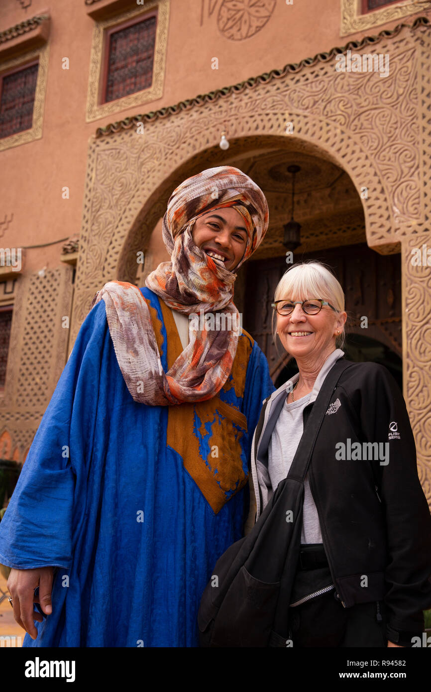 Morocco, Ouarzazate, man wearing traditional Berber tribal clothing with western tourist - Stock Image