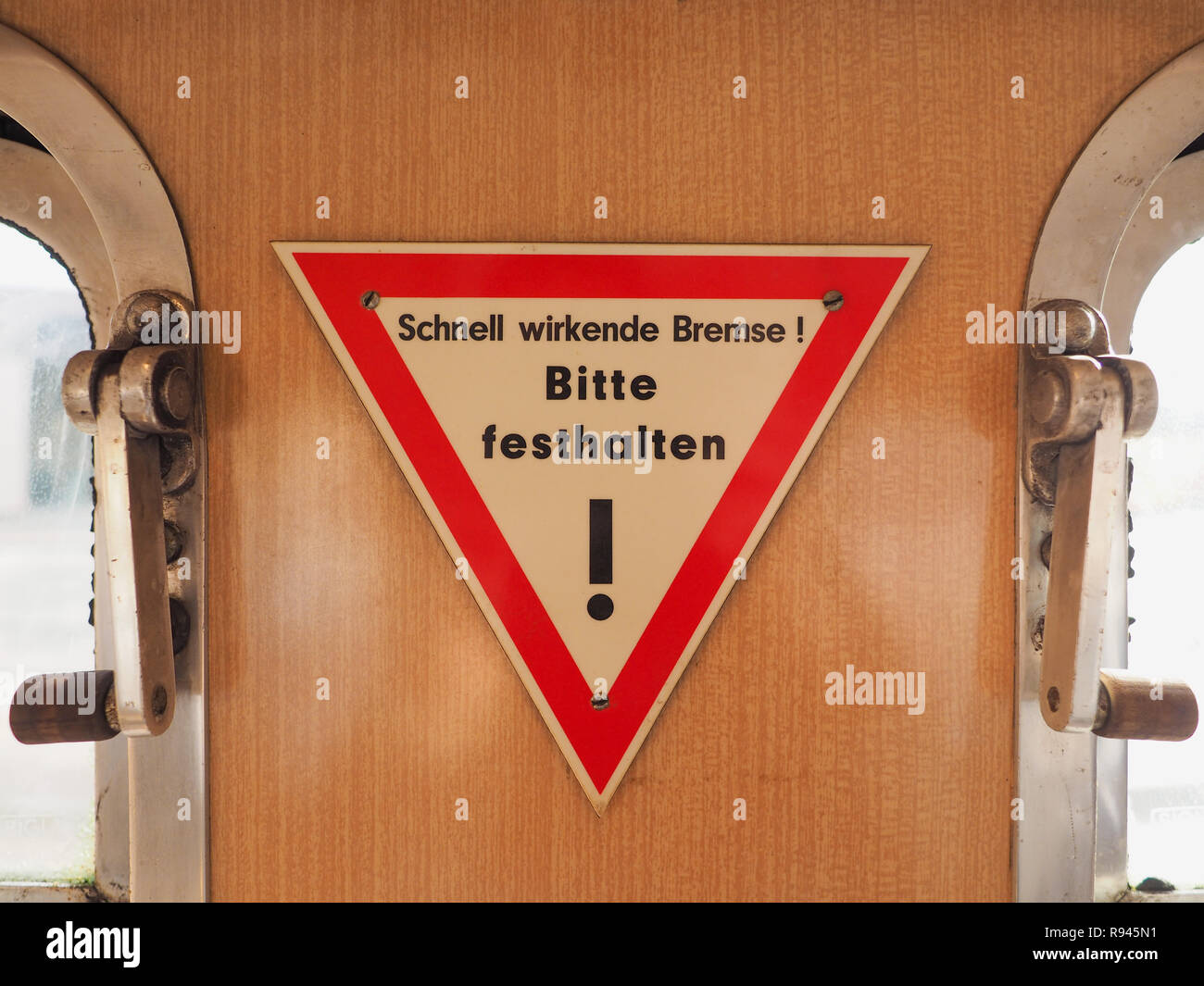 Schnell wirkende Bremse, Bitte festhalten (meaning Quick-acting brake, please hold tight) sign on vintage German tram - Stock Image
