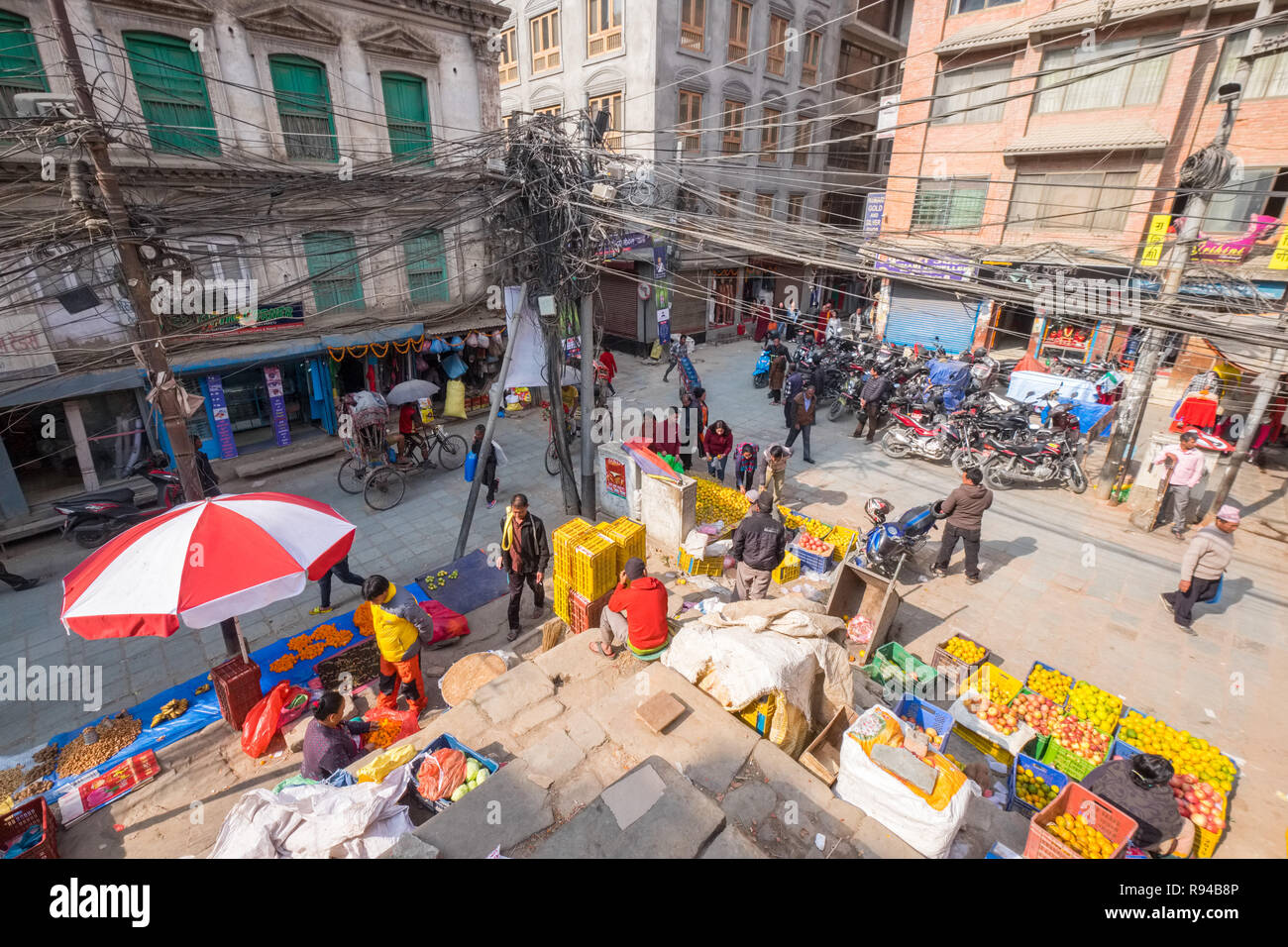 Busy crossroads in the old city Kathmandu, Nepal with a mass of overhead cables - Stock Image
