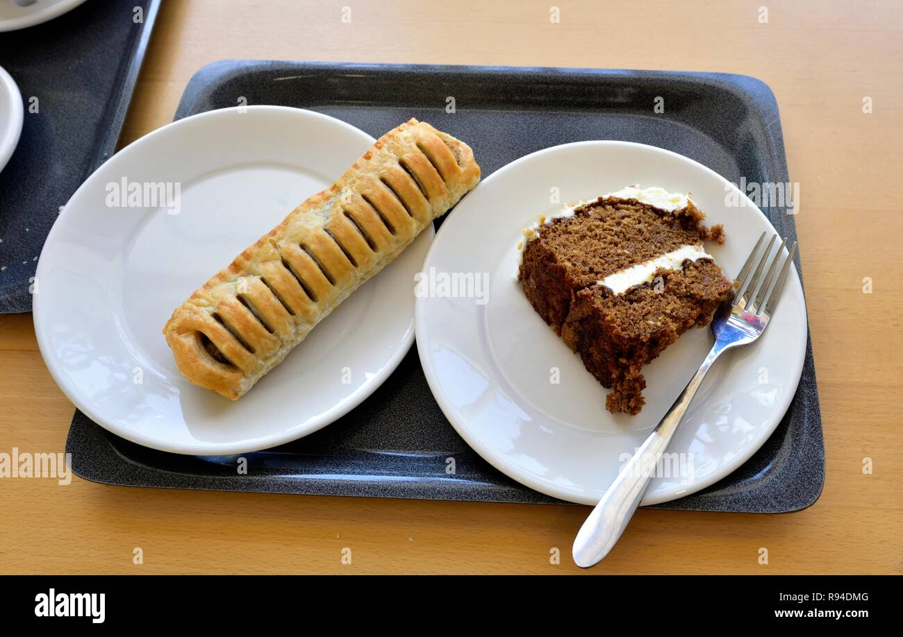 Sausage roll and chocolate cake on white plates and a serving tray. - Stock Image