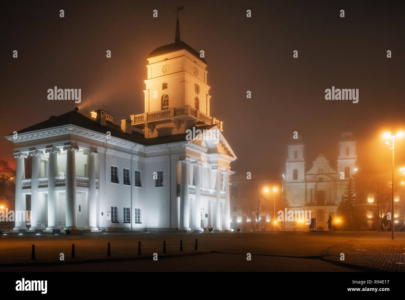 View of the Town Hall and Cathedral of the Holy Name of Mary in the fog in Minsk at night, Belarus - Stock Image