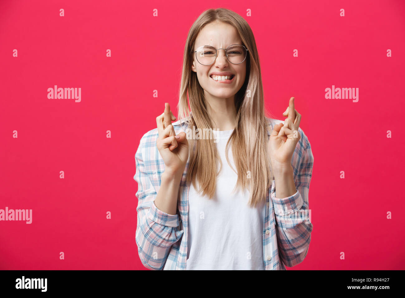 Portrait of wishful young woman in casual clothes with blonde dyed hair, crossing her fingers, biting her lower lip, feeling nervous before important event. Body language. - Stock Image