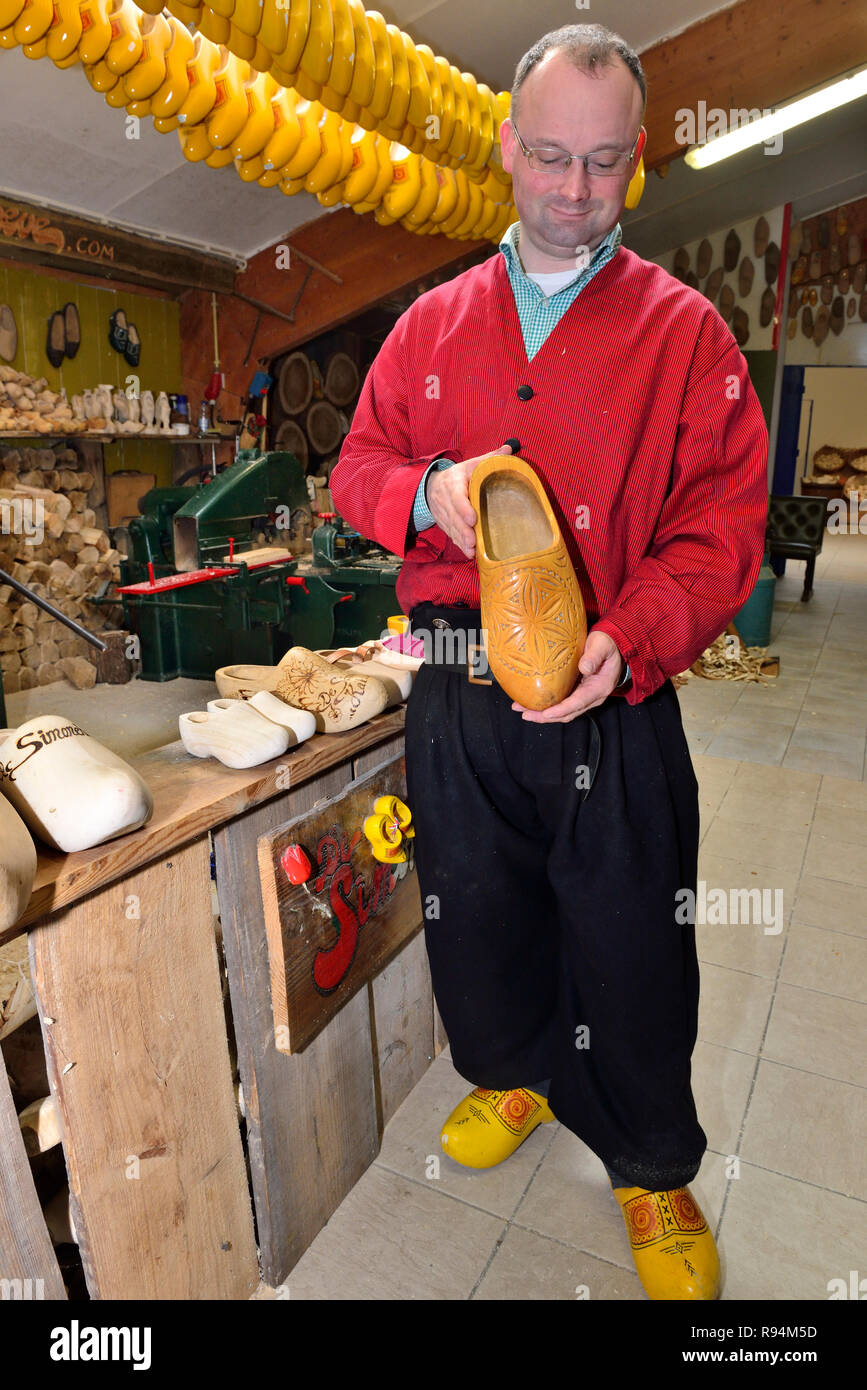 Man showing a yellow clog he has just make to tourists visiting  a small factory outside Volendam, North Holland, Netherlands Stock Photo