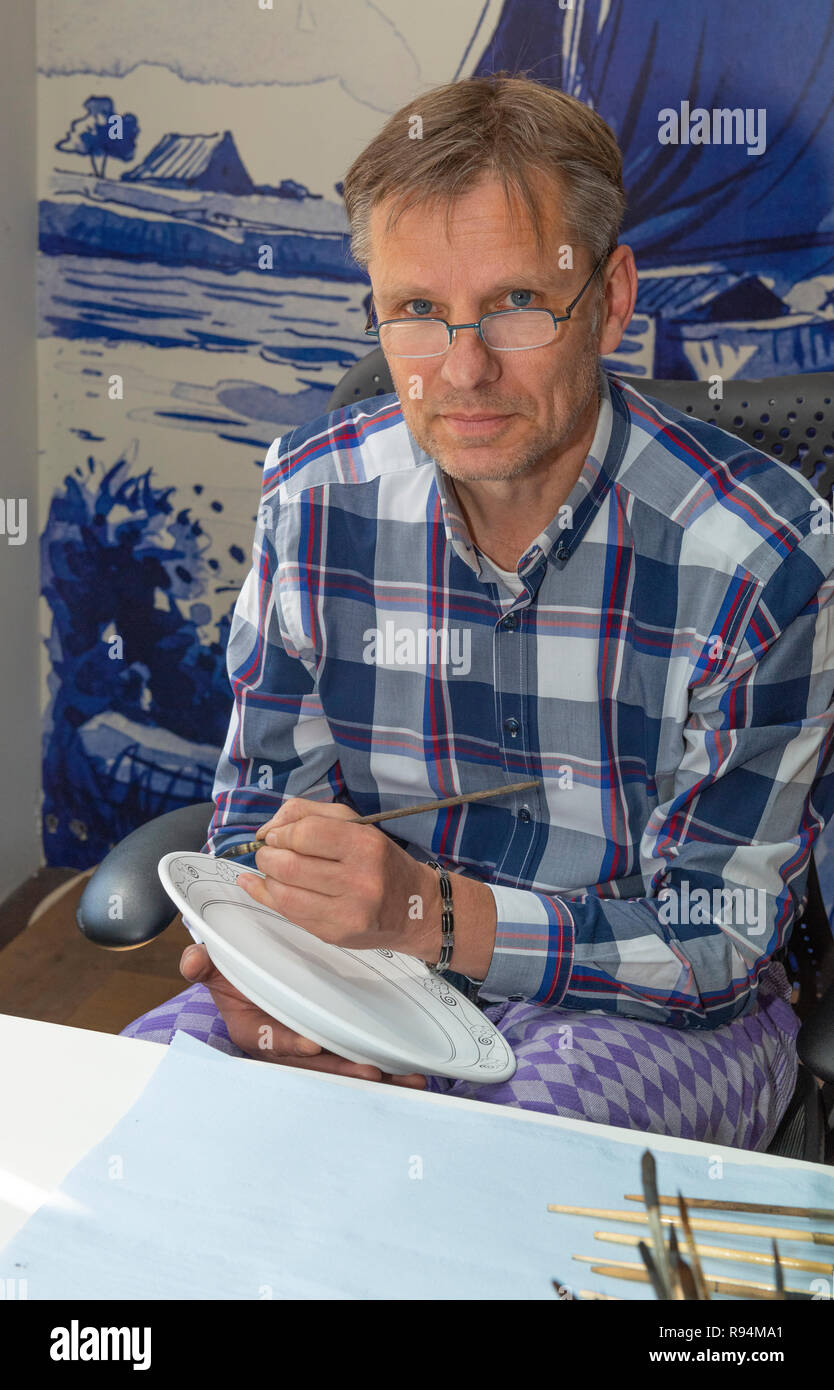 Male artist at the Royal Delft Pottery decorating a plate by hand, Delft, Holland, The Netherlands - Stock Image