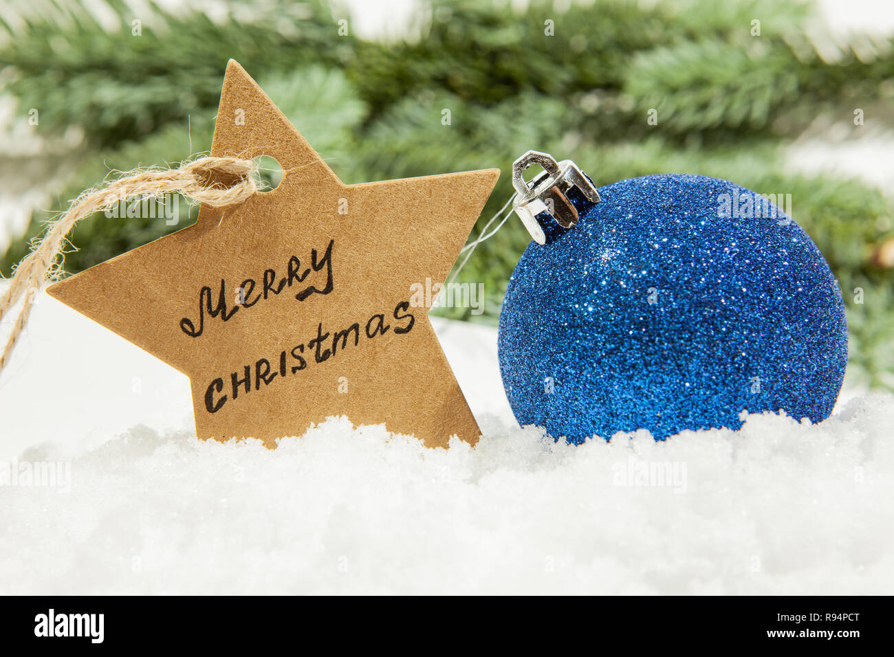 Christmas Ball In Blue On White Snow And A Star With The Inscription