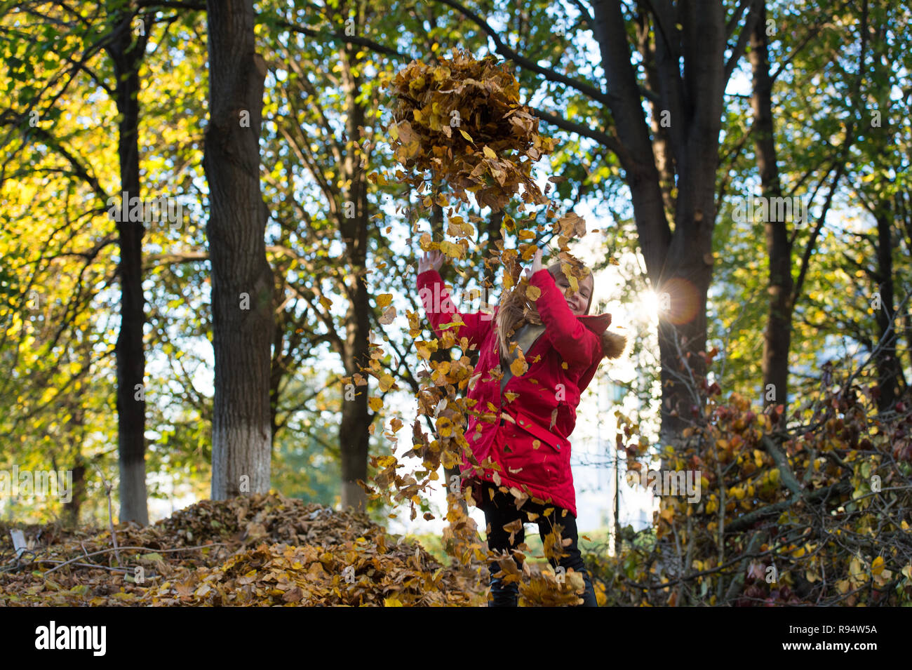 Fall clothes and fashion concept. Child blonde long hair walking fall park background. Girl happy wear coat with hood enjoy fall nature. Child wear coat for fall season. Baby play toss fallen leaves. - Stock Image