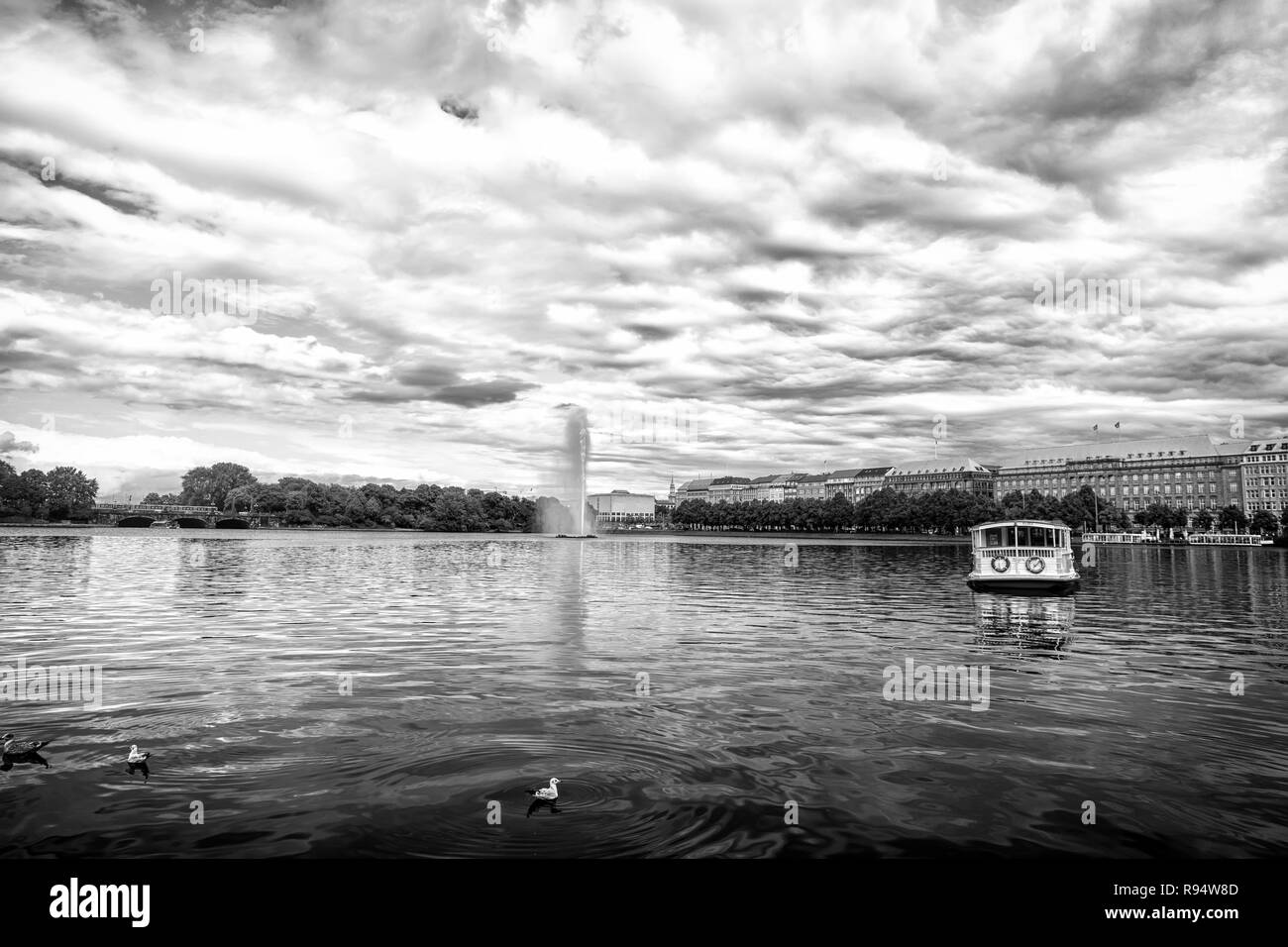 Lake with fountain in Hamburg city, Germany. Lake water on cloudy sky. Sightseeing landmark, attraction. Vacation travel wanderlust - Stock Image