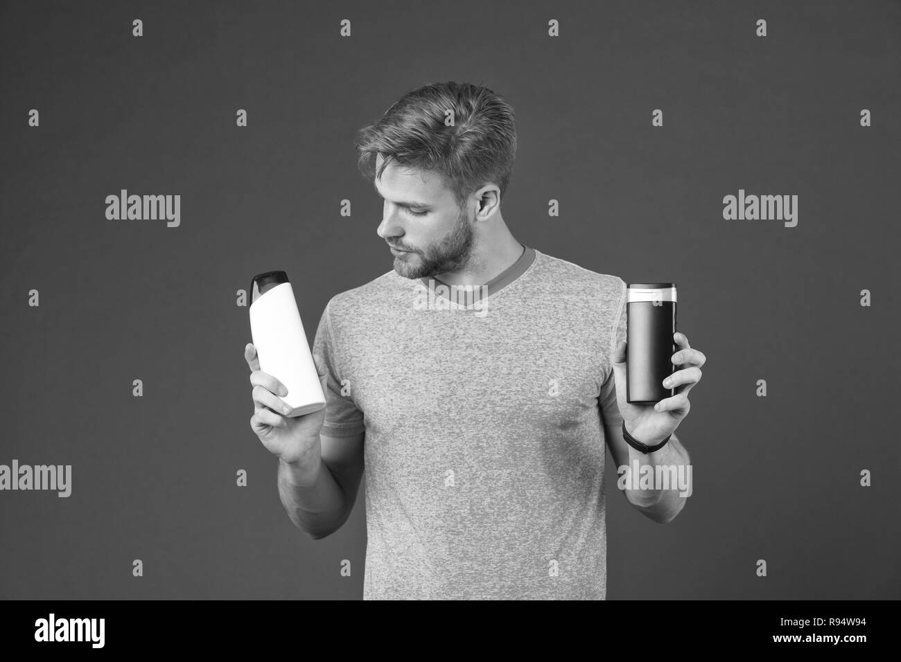 Man on thoughtful face chooses shampoo, violet background. Guy with bristle holds two bottles with shampoo, copy space. Man hesitates while making alternative decision. Hair care and shampoo concept. Stock Photo