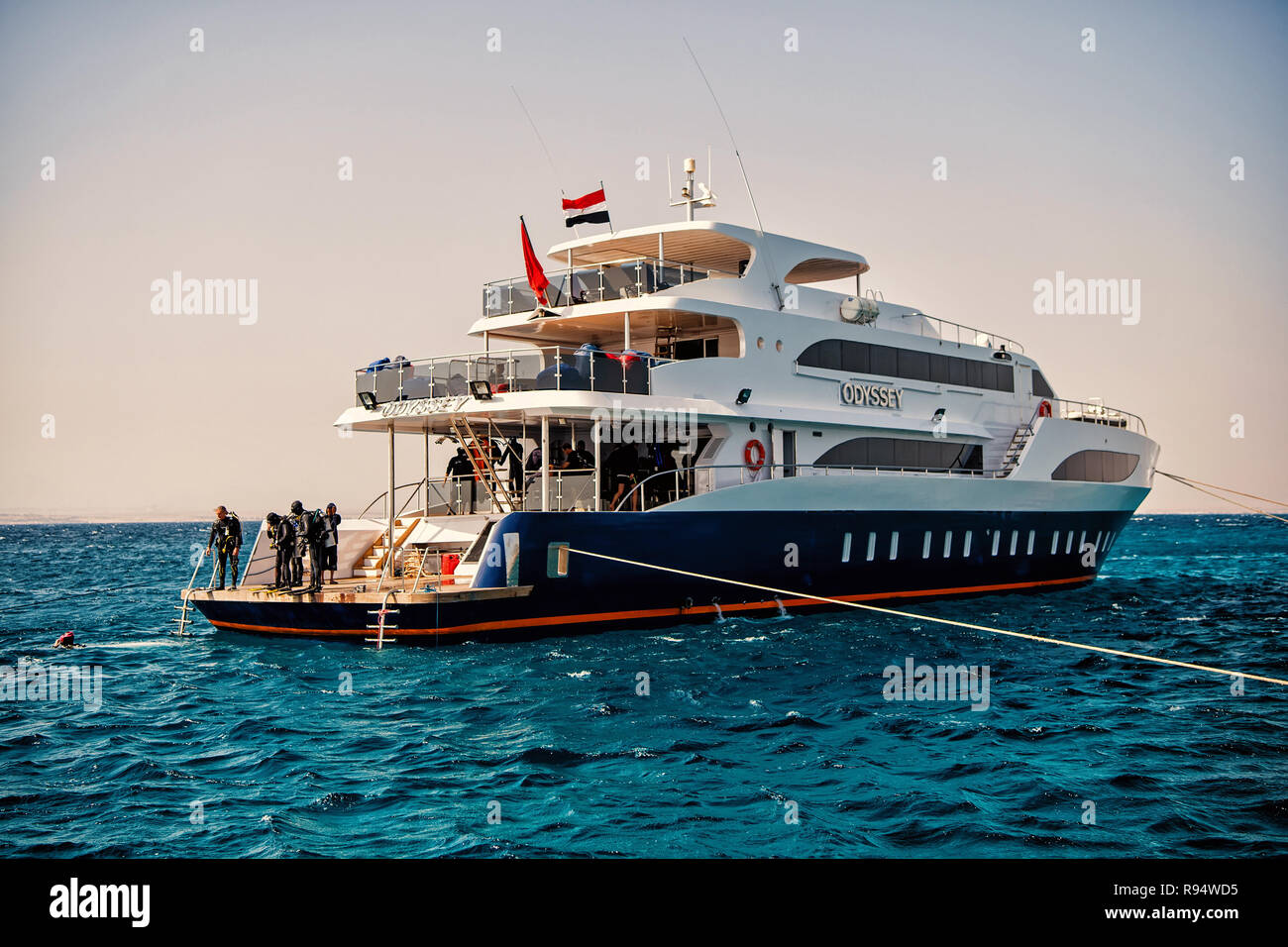 Hurghada, Egypt - February 24, 2017: white ship or yacht, modern motor boat and group of people, scuba divers, in wetsuits, snorkels in blue sea on summer day on clear sky. Snorkeling activity Stock Photo