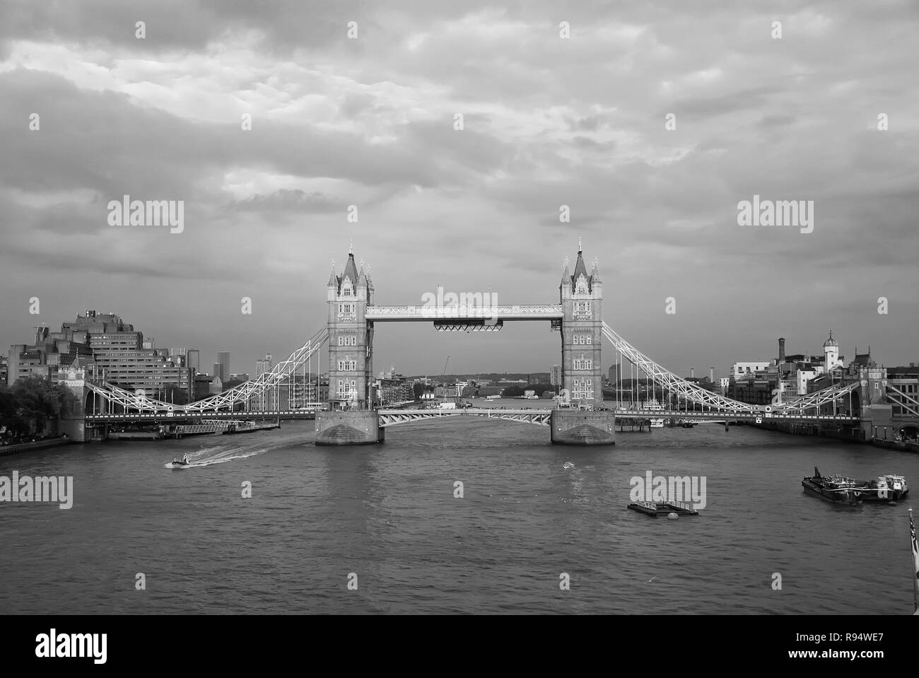 Tower bridge in London, United Kingdom. Bridge over Thames river on cloudy sky. Buildings on river banks with nice architecture. Structure and design. Wanderlust and vacation concept. - Stock Image