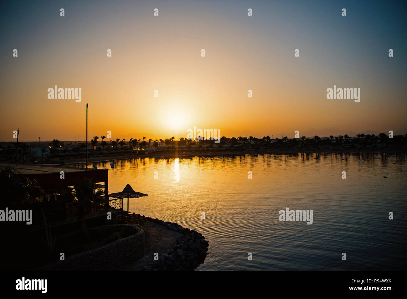 Calm tropical beach, sea or ocean water coast, of seaside resort with dark silhouettes of palm trees during sunset or sundown in evening dusk on clear, grey sky background. Idyllic summer vacation - Stock Image